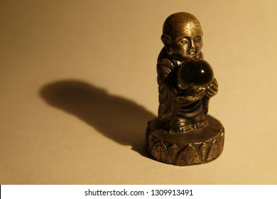 little happy enlightened monk buddha meditate, clear mind,  self-improving and comprehends nirvana on the background of brick (concrete jungle) with glass ball