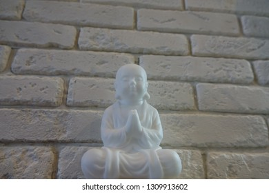 little happy enlightened monk buddha meditate, clear mind,  self-improving and comprehends nirvana on the background of brick (concrete jungle)