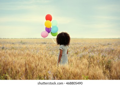 Little happy girl with balloons in the field