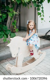 Little happy girl in color dress on white horse