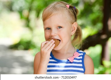 A little happy girl eats an avenaceous thin captain on nature.