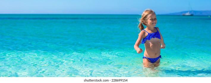 Little happy girl enjoying beach vacation