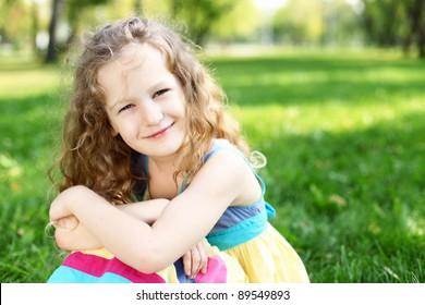 Little happy girl having fun in green summer park
