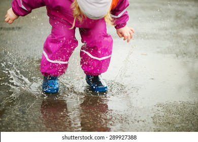Little happy girl jumping and having fun in puddle
