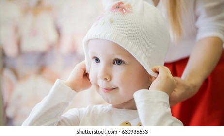 Little happy girl with mommy doing shopping and buying hat in kids dress store