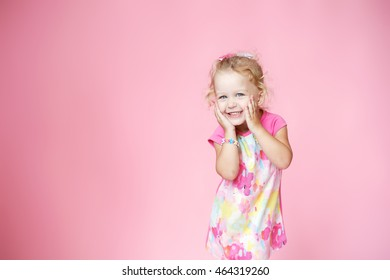 little happy girl in pink colored dress with blonde hair on pink background in Studio