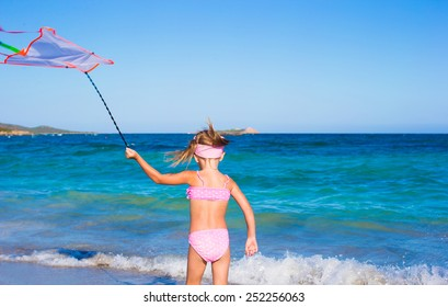 Little happy girl playing with flying kite during tropical beach vacation