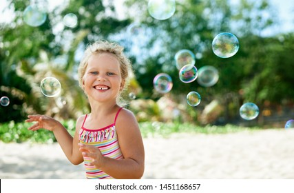 Little happy girl playing soap bubbles on the topical beach. Childhood, lifestyle concept