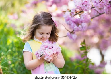 Child holding flowers images stock photos vectors shutterstock little happy girl playing under blooming cherry tree with pink flowers child holding sakura blossom mightylinksfo