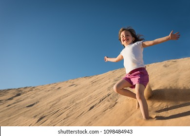 Little happy girl running down sand dune on sunny day with clear blue sky
