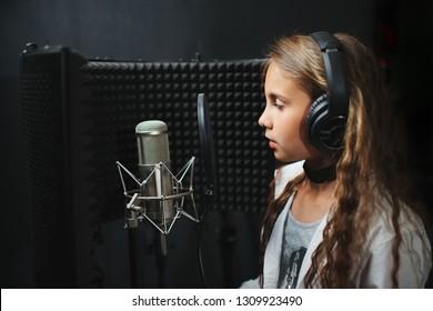 little happy girl singing in recording studio