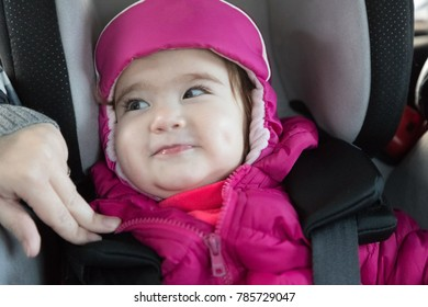 little happy girl sitting in a children's car seat close-up