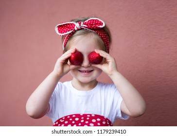 Little happy girl with strawberries. Healthy food for children. Kids eating.