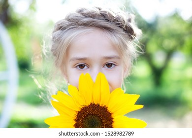 Little happy girl in summer park covers her face with a sunflower in summer, enjoys a sunny day and nature, expresses positive sincere emotions. A child plays with a sunflower. Childhood concept.