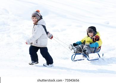 Little happy girl taking sled with little joyful boy, winter time