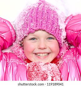 Little happy girl in winter pink hat in snow.