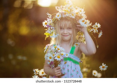 little happy girl in a wreath of daisies