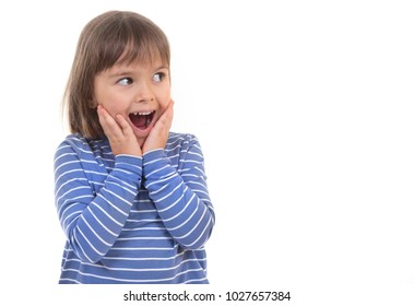 A little happy kid with an open mouth from a surprise is looking aside, against the white background for posting your information.