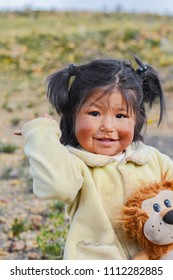 Little happy native american girl holding her toy lion in the countryside.