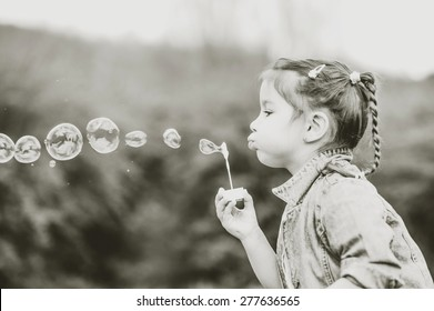 Little happy pretty girl blowing bubbles outdoor in the park
