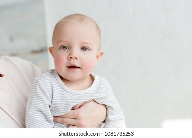 little happy son on mothers hands looking at camera