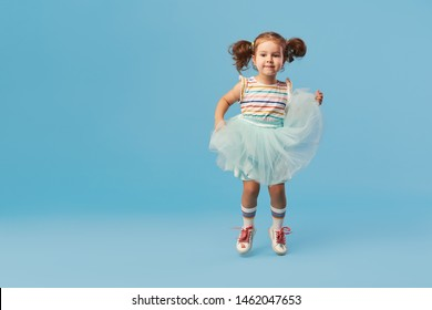 Little happy toddler child girl dreams of becoming ballerina in a cyan tutu skirt. Blue background. Space for text