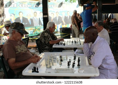 Little Havana, Miami, FL: Nov. 30, 2017 – Men of different cultures and colors play chess in historic Calle Ocho. In background is mural of Hispanic leaders who attended 1994 First Summit of Americas.