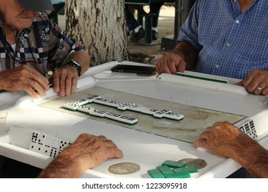 Little Havana, Miami, FL: Nov. 30, 2017 – Men of different cultures and colors play dominoes in historic Calle Ocho open space known as Domino Park. Elderly men's wrinkled freckled hands touch tiles.
