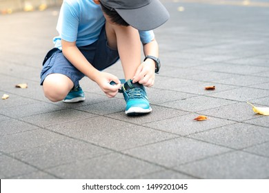 A little healthy asian schoolboy putting on his running shoes by himself in the playground. Life skills, Self-care, Montessori child, Comfortable kids shoes, Sport day, Outdoor fun, Get ready concept.