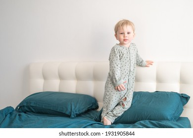Little healthy blonde toddler boy in green pajamas having fun in bed at home.