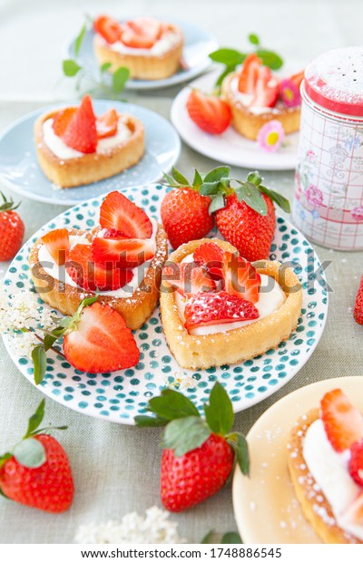 Little heart-shaped cake with fresh strawberries and cream
