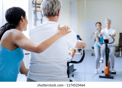 Little help. Kind attentive supporting medical worker putting her hand on a shoulder of a positive enthusiastic aged man while helping him to train on an exercise bike