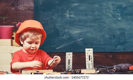 Little helper concept. Child dreaming about future career in architecture or building. Kid boy in orange hard hat or helmet, study room background. Boy play as builder or repairer, work with tools.