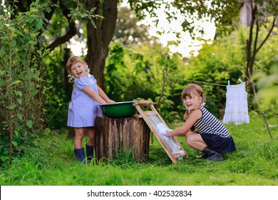 little helper girls washes white dress in a basin outdoors using the washboard outdoors