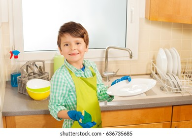 Little helper washing plates in the kitchen
