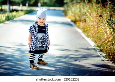 Little hip hop dancer. The little girl dressed as the hip-hopper is standing on a path in park