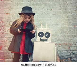 A little hipster child is wearing a cool hat and holding a tablet with her toy robot friend downtown for a happiness or technology concept.