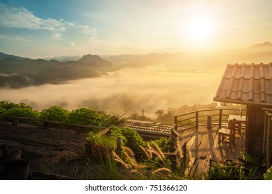 Little Home at Phu Langka National Park, Phayao Province, Thailand Golden sunrise above the high mountain foggy valley with old wooden houses on a hill.