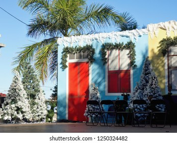 a little house decorated in a festive season in the sunny, evergreen Tenerife, with a blue sky and sunlit palm trees next to it.