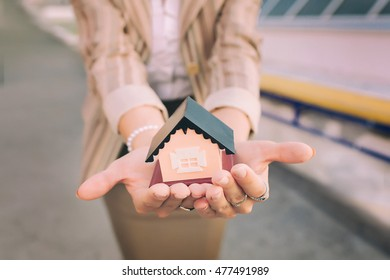 Little House in the hands of the girl in a business suit