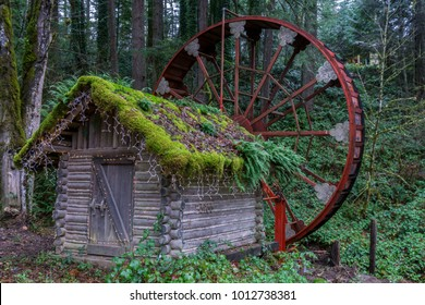 A little house with an old water mill  in the woods of a county park in Oregon