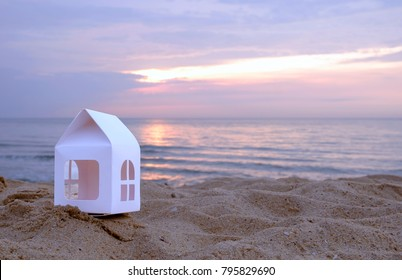 little house on the Beautiful beach with sunrise,copy space for advertising and text. Concept of vacation ,holiday or mortgage or real estate agent.