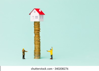 Little house on a pile of coins and two small builders controlling the stack of coins.