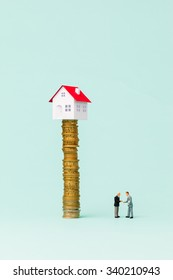 Little house on a pile of coins and two businessmen shaking hands.