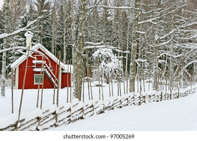 Little house painted in traditional Swedish red and brown colors, covered by snow.