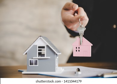 Little house toy on table with a key in woman hands