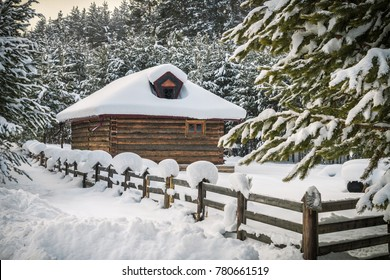 little house in the woods in winter, log cabin, wooden fence, snow