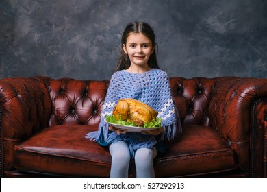 Little hungry girl sit on the sofa at night time and holding plate with tasty fried chicken. Taste food concept. Thanksgiving holiday.