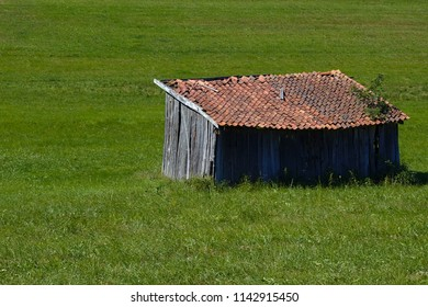 Little hut with red roof on a green meadow