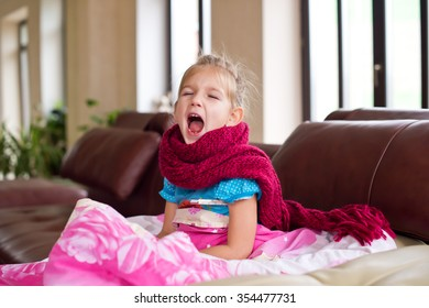 Little ill girl lies in bed with thermometer and scarf on neck getting well of flu